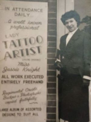 Jessie Knight pictured beside a poster displayed outside one of her shops, courtesy of Neil Hopkins-Thomas #JessieKnight #freehandtattooist #ladytattooist #historyoftattooing