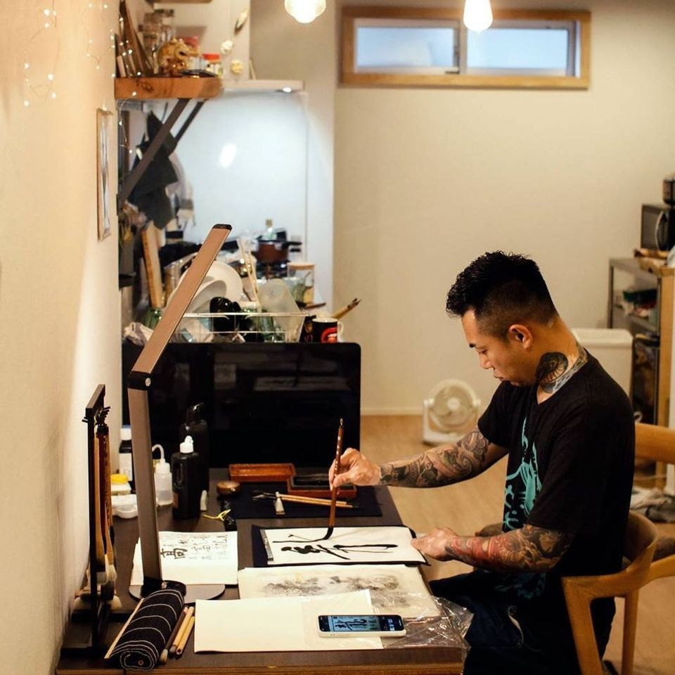 Ichi Hatano in his studio doing callipgraphy for the cover of his book