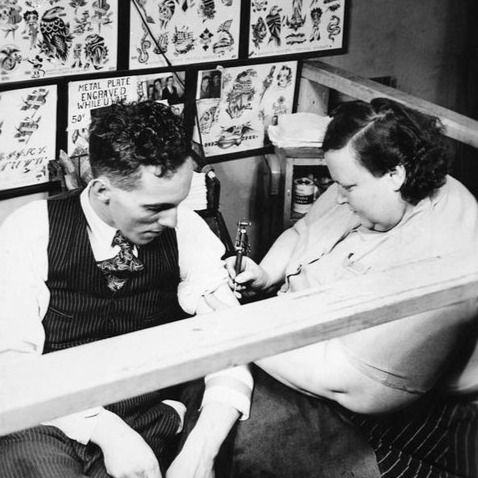 Dainy Dotty tattooing a client
