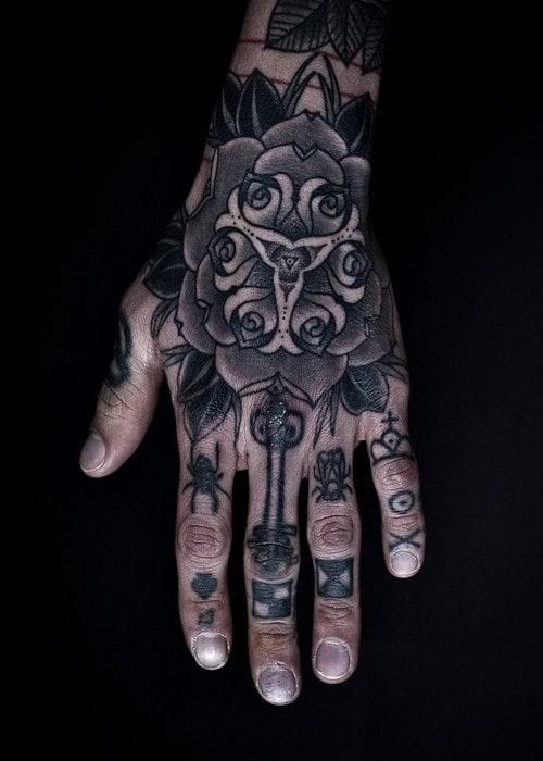 Choose a finger tattoo design that complements your hand tattoo well. Work by Thomas Hooper.
