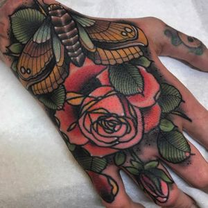 Moth and rose tattoo by Tyler Harrington #TylerHarrington #handtattoos #color #neotraditional #moth #insect #butterfly #wings #leaves #rose #rosebud #floral #flower #nature