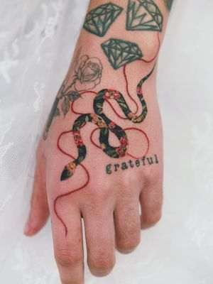Tattoo by Sion #Sion #snake #color #flower #floral #ribbon #reptile #handtattoo #tipping #tipyourartist #tippingmakesithurtless #tippingisappreciated