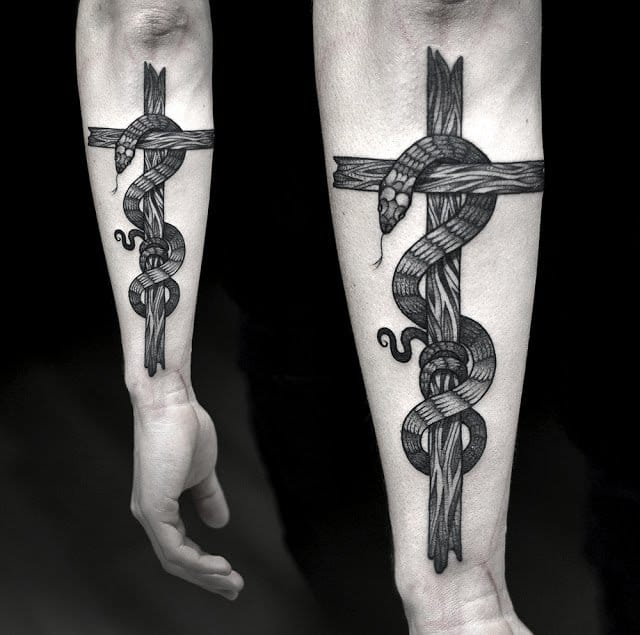 Here forming a cross in a jaw-droppping tattoo by Kamil Czapiga...