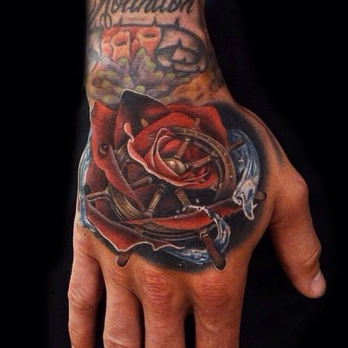 Rose and ship helm morph tattoo on Andres Acosta.