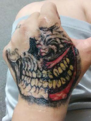 Half skull and half joker smile.