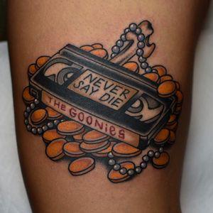 Never Say Die - rad Goonies tattoo by Tony Talbert #TonyTalbert #80stattoos #color #traditional #newschool #mashup #vhstape #coins #gold #pearls #bones #TheGoonies #movietattoo #Goonies #Neversaydie