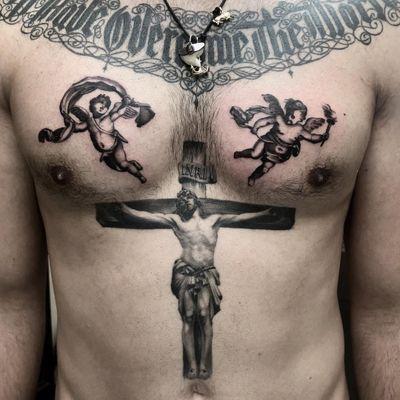 Tattoo by Lara Scotton #LaraScotton #religioustattoo #Christian #Catholic #religious #cross #jesus #jesuschrist #holy #cherubs #angels #wings #feathers #fire #crownofthorns #realistic #oldschool #blackandgrey