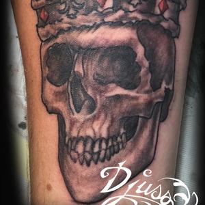 Crâne royal ou couronné en black and gray sur le bras d'un homme.