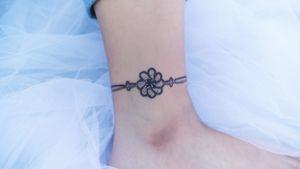 A purple knotted bracelet around the ankle. #tattoo #Korea #tattooart #koreatattoo #koreatattooist #flowertattoo #illustration #birthflowertattoo #tattooistartmag #hongdae #flowers #coloredtattoo #anklebracelet #watercolortattoo #hongdaetattoo #norigae #tattooistsion