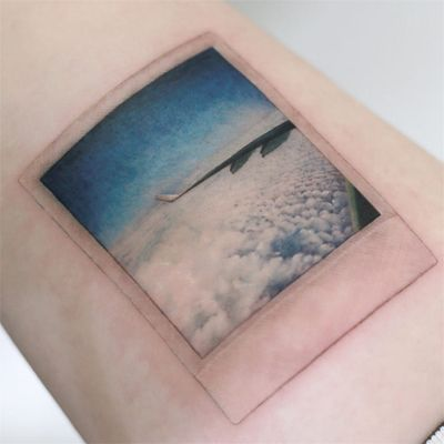 Tattoo by Tattooist Doy #TattooistDoy #realismtattoos #hyperrealismtattoos #realism #hyperrealism #realistic #airplane #travel #sky #polaroid #clouds