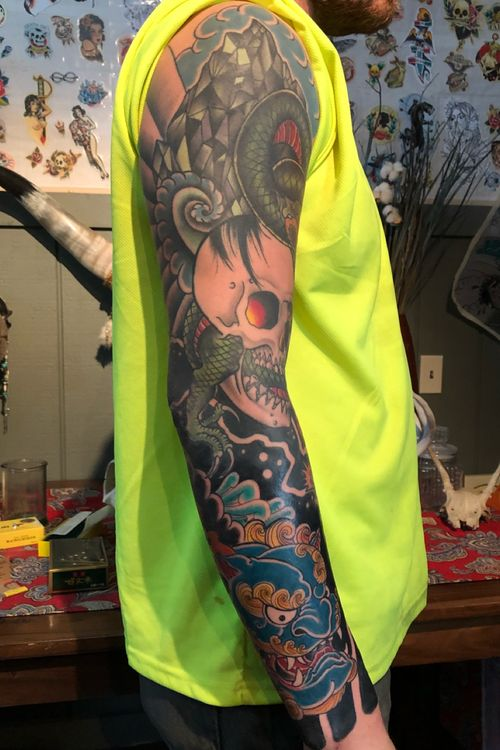 Traditional sleeve skull, dragon, snake, foo dog. The top is a cover up. There was some 90's tribal on the upper arm.