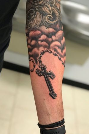 Freehand Black and gray Rosary wrapping around the forearm. Reworked the clouds a bit above to blend into current work.