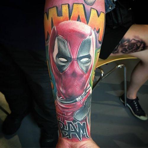 Deadpool colour realism tattoo on forearm, with onomatopoeia embelishment.