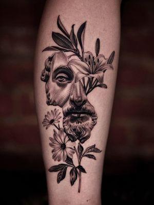 Broken Marcus Aurelius with flowers on leg.