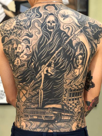 Chicano tattoo by #AlejandroLopez #chicano #chicanotattoo #blackandgrey #traditional #oldschool #illustrative #reaper #car #lowrider #barbedwire #weed #cards #dice #lips #jail #scythe #skull #backpiece #back