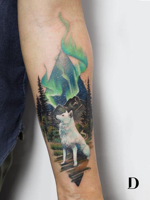Beautiful tattoo by Deborah Genchi #DeborahGenchi #debartist #realism #realistic #illustrative #watercolor #color #wolf #animal #mountain #landscape #nature #stars #sky #trees #auroraborealis #forearm #arm