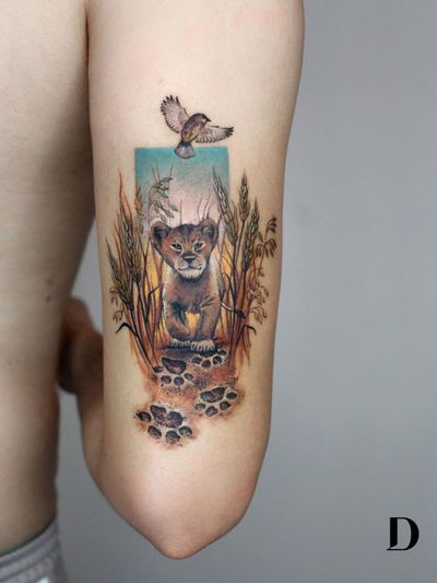 Beautiful tattoo by Deborah Genchi #DeborahGenchi #debartist #realism #realistic #illustrative #watercolor #color #lioncub #babyanimal #animal #nature #cute #bird #lionking #pawprints #upperarm #arm
