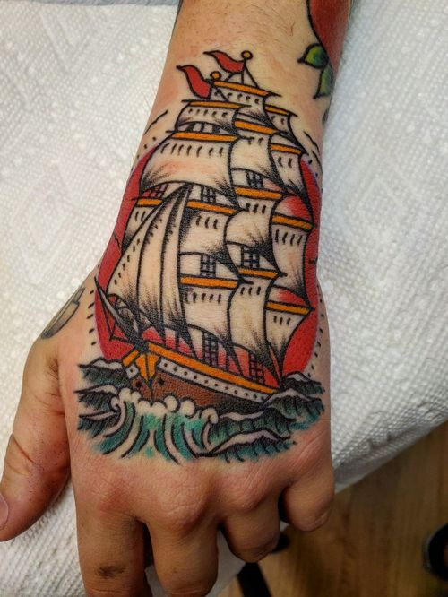 Traditional ship at sea with sunset hand tattoo