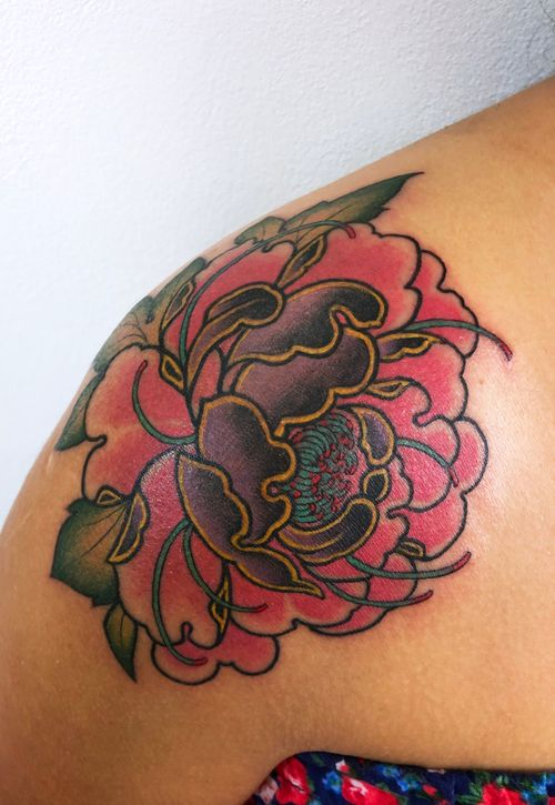 Sweet peony on tanned shoulder