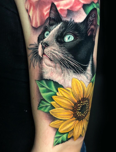 Verified Details from this super cute black and white kitty and sunflower I tattooed recently at @gritnglory 😻🌻 I would normally add some more detail in the leaves, but wanted to match them to some already existing leaves around the above rose tattoo not done by me. I'm always excited to tattoo animals and flowers! #realism #realismcat #cat #cattattoo #sunflower
