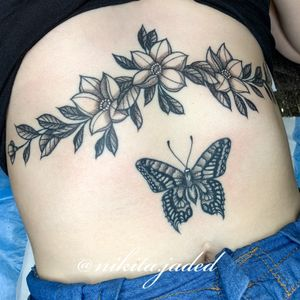 Floral sternum tattoo and butterfly above the naval