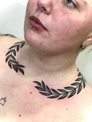 Corona de laurel sobre el cuello.