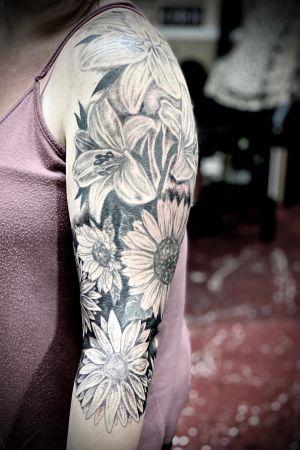 Floral sleeve. #floraltattoo #blackandgrey #sunflowertattoo #daisytattoo #lilytattoo #realismtattoo