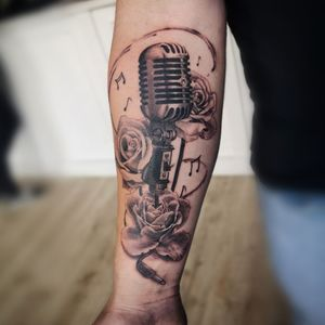 Microphone with roses. Arm tattoo, black and grey