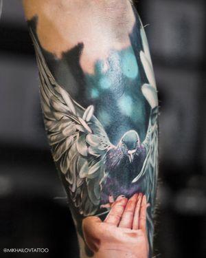 Realistic colorful tattoo of a dove by tattoo artist Alexei Mikhailov @mikhailovtattoo