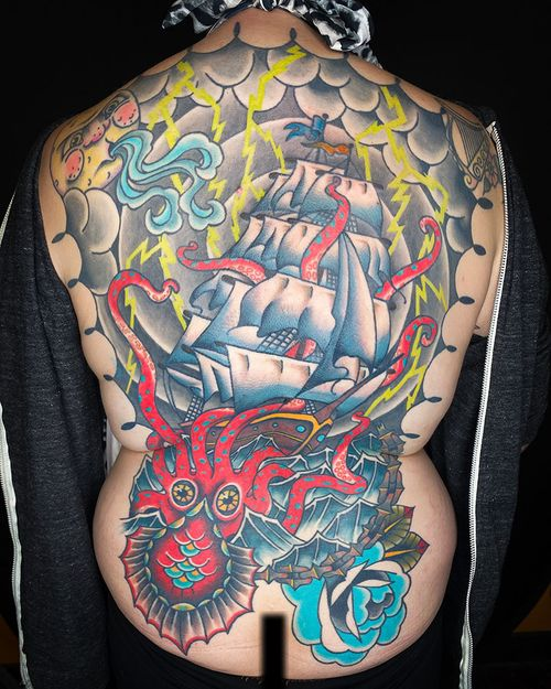 Full back tattoo featuring a kraken, ship and a little moon face blowing a storm around.  Most of the tattoo is healed and settled over a year (thanks, global pandemic).  We were finally able to finish up coloring the sails after the client and I were both vaccinated.