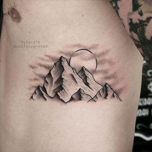 Mountain tattoo on the ribs.