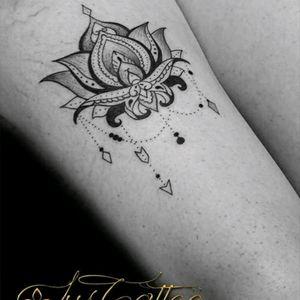 Tatouage fleur de lotus sur la cuisse d'une femme avec des perles des bijoux qui lui coule sur la cuisse