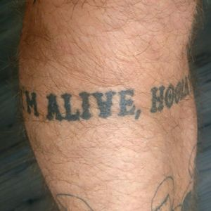 It says I'm Alive, Hooray From a Queens Of The Stoneage track Done at The Black Lodge I forgot the artist! Sorry for shit image, but it wraps