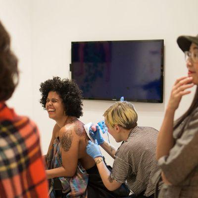 "Emily North tattoos fellow artist Awilda Rodríguez Lora on a livestream at SOHO20 Gallery for their collaboration ""Still Life, Still Alive"" (Photo by Amar Puri.) #Art #Feminism #LiveTattoo #NYC #EmilyNorth #Em16 #AwildaRodríguezLora"