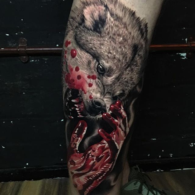 The color contrasting in this tattoo by Ash Higham (IG—ashhighamtattoos) brings out the violence of the scene. #animals #AshHigham #blood #blackandgrey #color #hand #realism #wolf