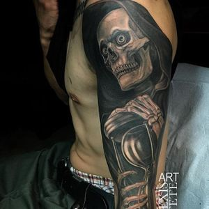 Time is running out when you see the grim reaper holding an hourglass. By Alexis Vaatete. #blackandgrey #realism #AlexisVaatete  #grimreaper #skull #skeleton #hourglass