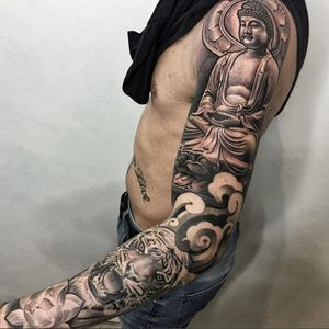 A sleeve topped off with a stonelike Buddha by Lil B (IG—lilb_tattoos). #blackandgrey #Buddha #LilB #tiger