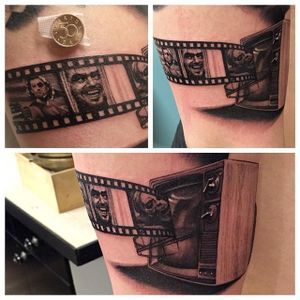 Tiny, but incredibly detailed, television and film strip tattoo by Jens Bergstrom. #blackandgrey #realism #television #film #JensBergstrom