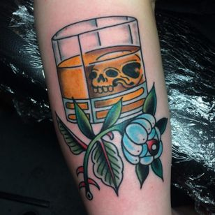 Tattoo by Sam Ricketts, photo from Sam's Instagram. #skull #traditional #oldschool #whiskey #flower