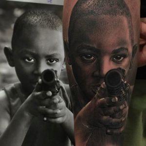 A stunning portrait of a kid pointing a gun, tattoo by Fredy Tomas. #FredyTomas #ExoticTattoo #realistictattoo #blackandgrey #portraittattoo
