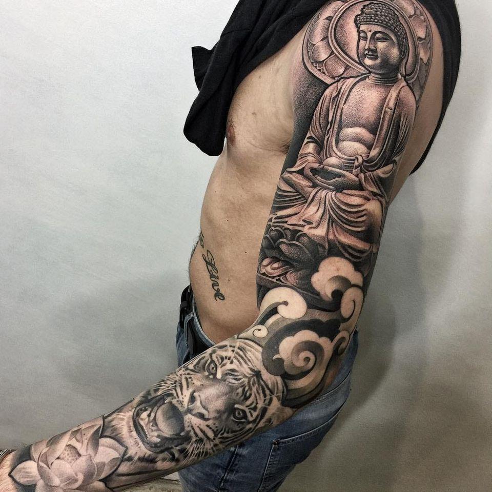 Buddha tattoo by Lil B #LilB #buddhisttattoos #blackandgrey #realism #realistic #hyperrealism #clouds #tiger #junglecat #buddha #buddhism #pattern #lotus #stonework #sculpture #mudra #meditation