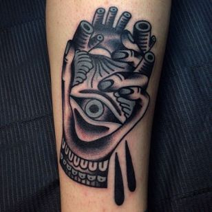 Solid tattoo of a hand holding an anatomical heart with an eye. Bizarre tattoo by Rodrigo Garcia Delgadillo. #rodrigogarciadelgadillo #hand #heart #eye