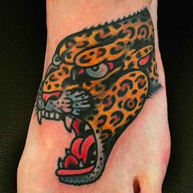 Leopard head tattoo on foot done by Alex WIld. #AlexWild #traditionaltattoo #boldtattoos #leopard #leopardhead