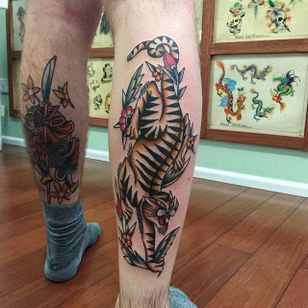 A killer tiger tattoo with floral accents via Tommy Doom (IG—tommydoom). #tiger #TommyDoom #traditional