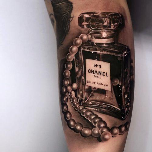 Chanel tattoo by Christos Galiropoulos #ChristosGaliropoulos #fashiontattoo #blackandgrey #realism #realistic #hyperrealism #glass #perfume #pearls #perfumebottle #bottle #Chanel #fashion #style #tattoooftheday