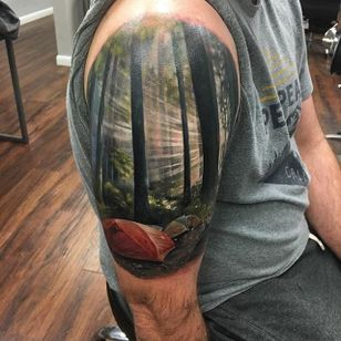 Sun streaming through the trees makes camping look all the more beautiful. Tattoo by Kyle Cotterman. #realism #colorrealism #KyleCotterman #trees #sunlight #camping #landscape