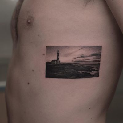 Lighthouse tattoo by Fillipe Pacheco #fillipepacheco #landscapetattoo #blackandgrey #realism #realistic #hyperrealism #landscape #ocean #mountain #building #lighthouse #sky #clouds #architecture