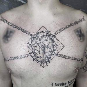 Rad tattoo composition and clean execution, chained heart tattoo by Gabor Zolyomi. #GaborZolyomi #FatumTattoo #blackwork #illustrativetattoo #heart #chains #chest