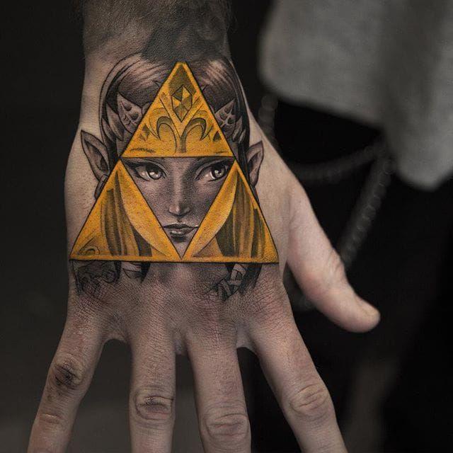 Niki Norberg's take on Princess Zelda and the Triforce. Save her from the evil Ganondorf, Link! #bangers #blackandgrey #color #NikiNorberg #photorealism #realism #Triforce #Zelda #gamertattoos #nintendo