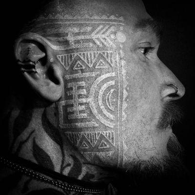 White ink tribal tattoo by Watsun Atkinsun #WatsunAtkinsun #whiteinktattoos #facetattoo #tribal #geometric #linework #shapes #triangle #moon #dotwork #dots #circle #ornamental #tattoooftheday